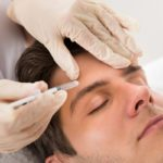Man Having Botox Injected Near His Eyebrow Area