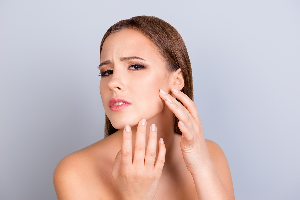 woman looking at her pimple